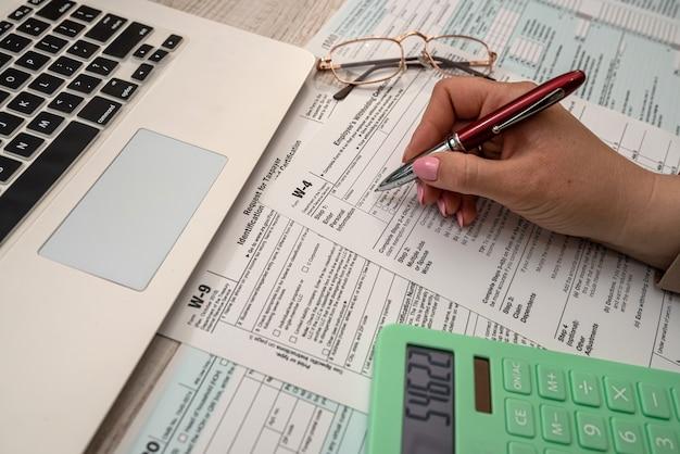 Vrouw werkt met vs belastingformulier 1040 en rekenmachine laptop op kantoor. boekhoudconcept