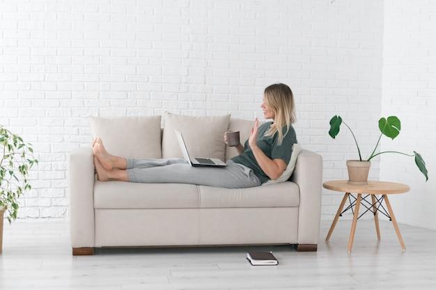 Vrouw werkt of leert vanuit huis met een notebook, videochats of online conferentie, leg op de bank