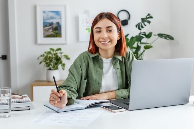 Vrouw werkt op afstand thuis met laptopcomputer jonge zakenvrouw die haar tijd plant