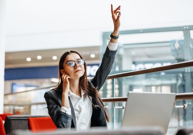 Vrouw werkt op een laptop en belt een collega op de werkvloer
