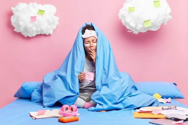 Vrouw werkt 's avonds laat met deadline gaapt en tegens mond gewikkeld in deken drinkt koffie wil slapen bereidt zich voor op examen doet papierwerk