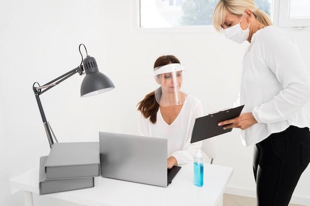 Vrouw werkt samen en draagt gezichtsbescherming