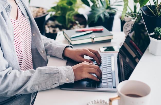 Vrouw werkt thuis aan schone natuurwerkruimte met laptop, planner-notitieboekje en rekenmachine. zakelijke financiën office concept.