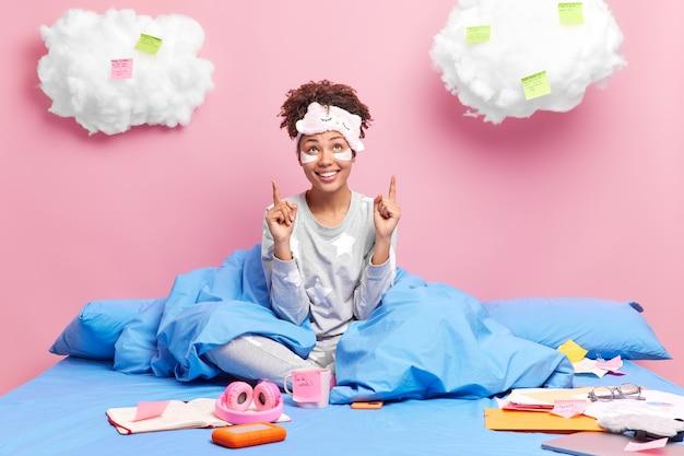 Vrouw werkt vanuit huis geniet van afgelegen werk poiten boven op wolken draagt slaapmasker en pyjama zit gekruiste benen in bed omringd door papieren aantekeningen bereidt project voor