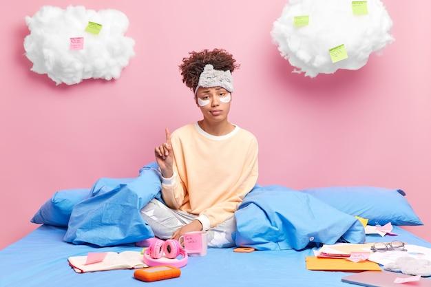 Vrouw werkt vanuit huis op zelfisolatiepunten hierboven met wijsvingers gekleed in pyjamahoudingen in slaapkamer maakt notities en lijst om te doen. thuiswerken op afstand