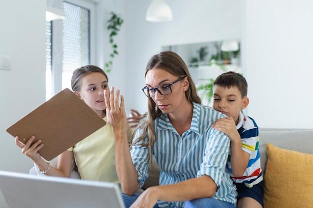 Vrouw werkt vanuit huis tijdens quarantaine met haar zoontje en dochtertje op de bank en schreeuwend, aandacht eisend