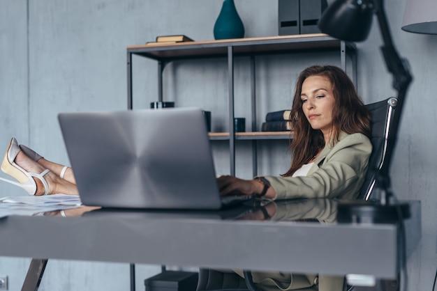 Vrouw werkt zittend met haar benen op haar bureau.