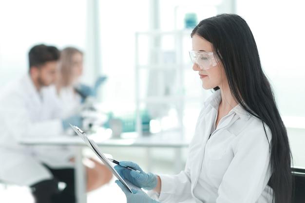 Vrouw wetenschapper lezen van notities in een laboratoriumjournaal close-up