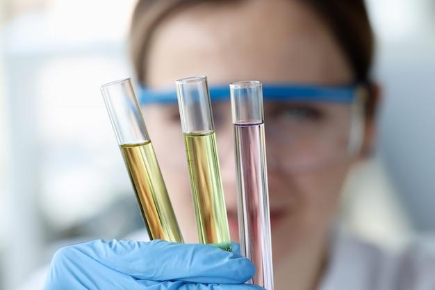 Vrouw wetenschapper reageerbuisjes met veelkleurige vloeistoffen houden in haar handen close-up. laboratoriumanalyse van geneesmiddelenconcept