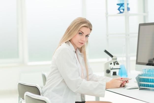 Vrouw wetenschapper zit aan een bureau in het laboratorium. wetenschap en gezondheid