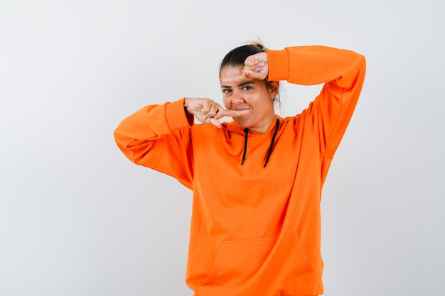 Vrouw wijst naar beide kanten in oranje hoodie en ziet er zelfverzekerd uit