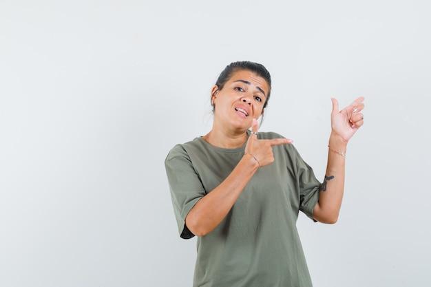 Vrouw wijst naar de zijkant in t-shirt en kijkt zelfverzekerd