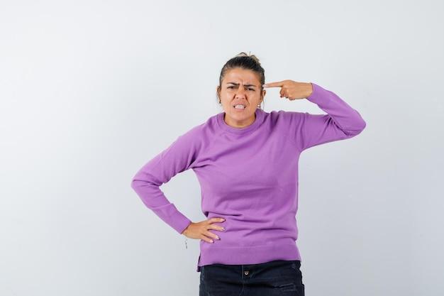 Vrouw wijst naar haar hoofd in wollen blouse en kijkt hatelijk