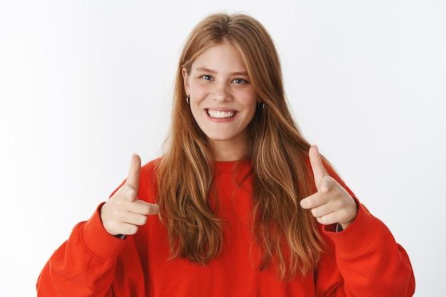 Vrouw wijst naar voren alsof ze de persoon aanwijst die ze kiest glimlachend in het algemeen vriendelijk en aangenaam zijnde keuze maken of groeten vriend, poserend in een knus warm sweatshirt over grijze muur