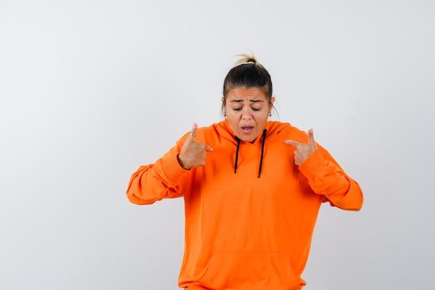 Vrouw wijst naar zichzelf in oranje hoodie en kijkt gealarmeerd