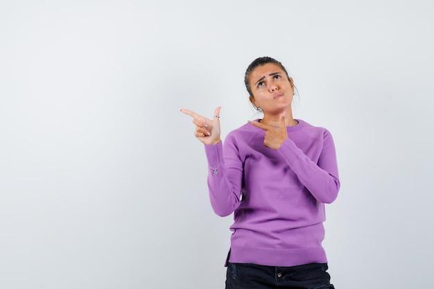 Vrouw wijst opzij in wollen blouse en kijkt aarzelend