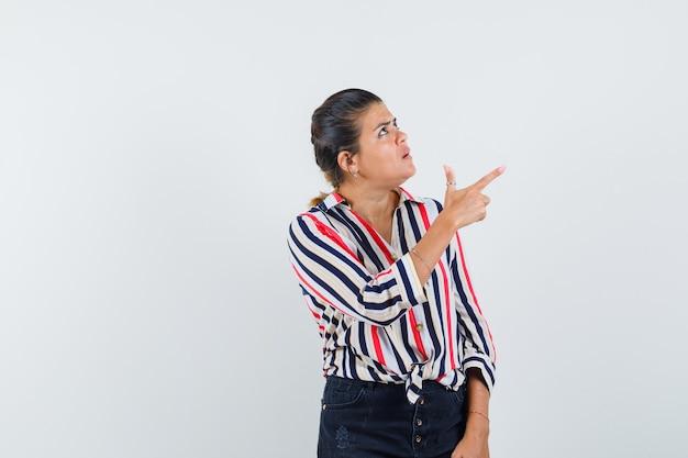 Vrouw wijzend naar de rechterbovenhoek in shirt, rok en kijkt gefocust