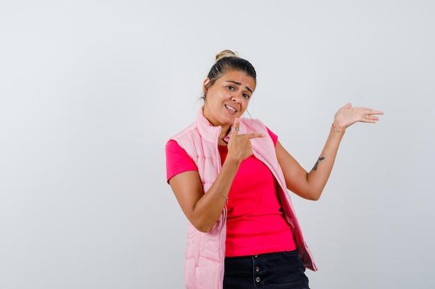 Vrouw wijzend naar iets dat deed alsof het werd vastgehouden in t-shirt, vest en er vrolijk uitzag