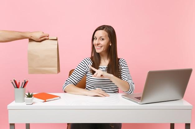 Vrouw wijzend op bruine duidelijke lege lege ambachtelijke papieren zak, werk op kantoor met laptop geïsoleerd op roze achtergrond. koeriersdienst voor het bezorgen van voedselproducten van winkel of restaurant naar kantoor. ruimte kopiëren.