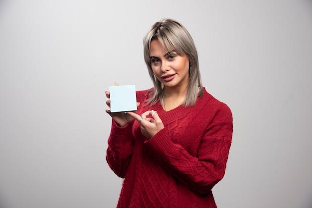 Vrouw wijzend op memo pad op grijze achtergrond.