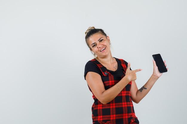 Vrouw wijzend op mobiele telefoon in overgooier jurk en op zoek zelfverzekerd. vooraanzicht.