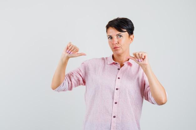 Vrouw wijzend op zichzelf met duimen in roze shirt en kijkt zelfverzekerd, vooraanzicht.