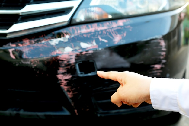 Vrouw wijzende vinger naar een bekraste auto vraag om hulp. autoverzekering Premium Foto