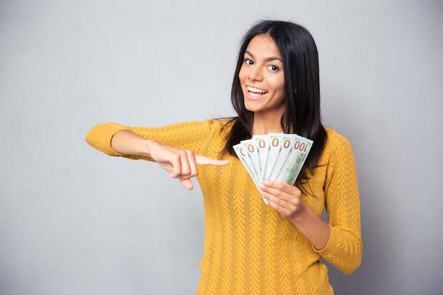 Vrouw wijzende vinger op dollarbiljetten