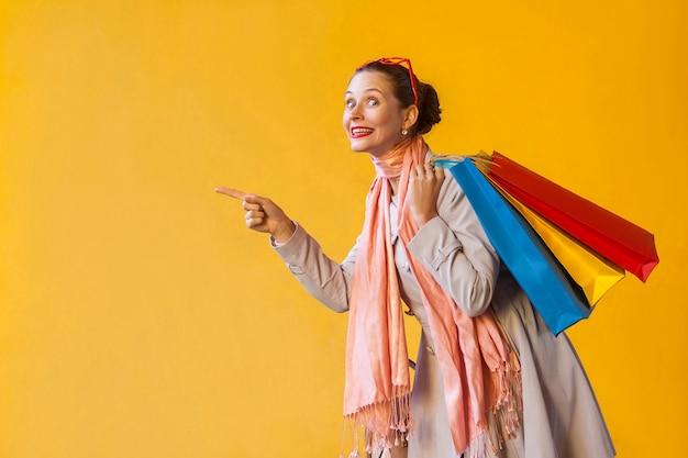 Vrouw wijzende vinger op kopieerruimte en kijken naar camera en brede glimlach op gele achtergrond