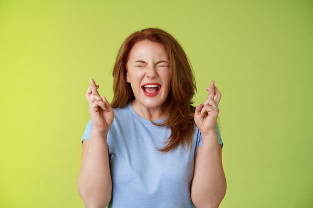 Vrouw wil winnen erg enthousiast gelukkig roodharige vrouw van middelbare leeftijd smeken smeken god laat droom uitkomen kruis vingers veel geluk wensen gesloten ogen open mond opwinding groene muur