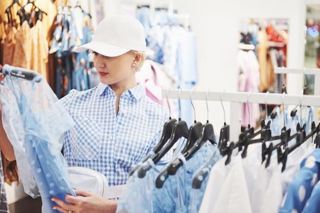 Vrouw winkelen kleding. klant die binnen kleding in opslag bekijkt. mooi gelukkig lachend aziatisch kaukasisch vrouwelijk model