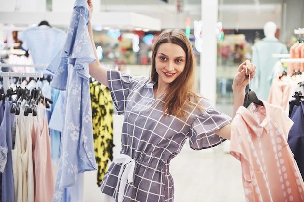 Vrouw winkelen kleding. klant die kleding binnen in opslag bekijken. mooi gelukkig lachend aziatisch kaukasisch vrouwelijk model