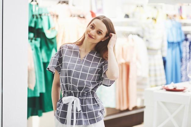 Vrouw winkelen kleding. klant die kleding binnen in opslag bekijken. mooi gelukkig lachend kaukasisch vrouwelijk model