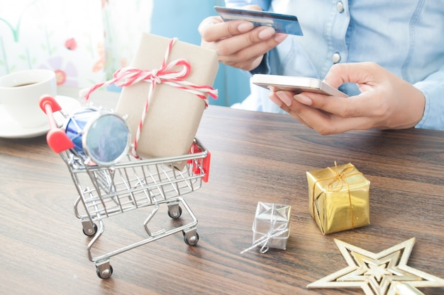 Vrouw winkelen online met creditcard en mobiele telefoon, focus op winkelwagen met cadeau doos