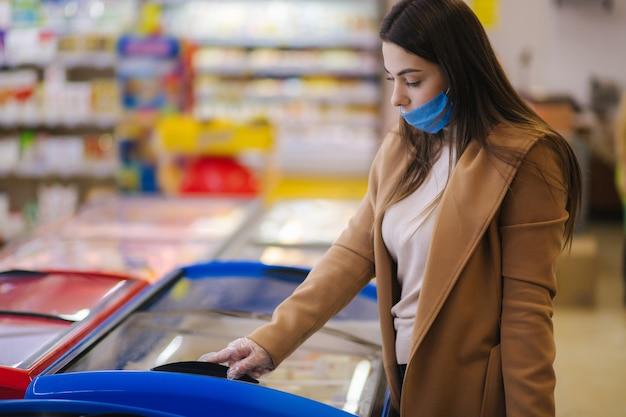 Vrouw winkelen tijdens de coronavirus covid-19 pandemie. een jonge vrouw koopt halffabrikaten van
