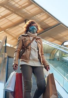 Vrouw winkelt in een winkelcentrum met gezichtsmasker, nieuw normaal, covid-19