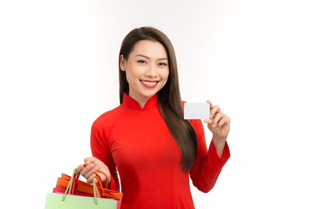 Vrouw winkelt in vietnamese traditionele klederdracht en houdt boodschappentassen vast terwijl ze creditcard toont