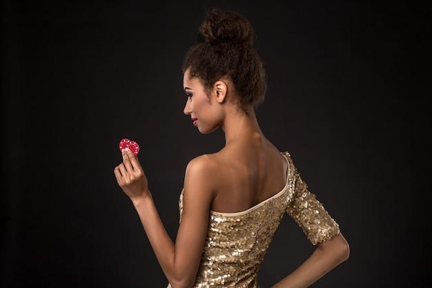 Vrouw winnende jonge vrouw in een stijlvolle gouden jurk met twee rode fiches en een poker of azen kaart combina...