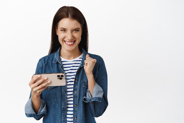 Vrouw wint op mobiel videogame, houdt smartphone horizontaal en kijkt tevreden, kijkt naar iets op telefoon op wit