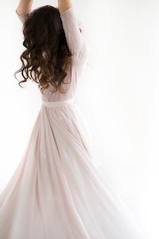 Vrouw witte jurk, mannequin in lange zijden jurk, zwaaiende vliegende stof, fladderende op wind