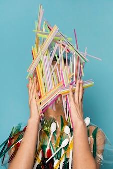 Vrouw wordt bedekt met kleurrijke plastic rietjes en tafelgerei