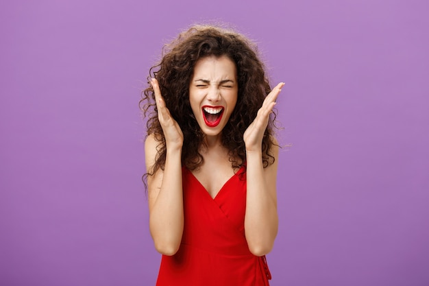 Vrouw wordt gek, schreeuwend, gespannen onder druk, ogen sluitend handen schuddend en schreeuwend, verdrietig en overstuur, de controle verliezend over emoties die ontevreden en beu zijn over een paarse achtergrond.
