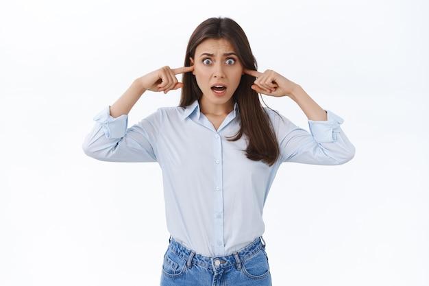 Vrouw wordt gek van luide vreselijke muziek die buren speelt, klaagt over lawaai, grimassen, gehinderd en ontevreden, voel enorm ongemak, stop vingers in oren, witte muur