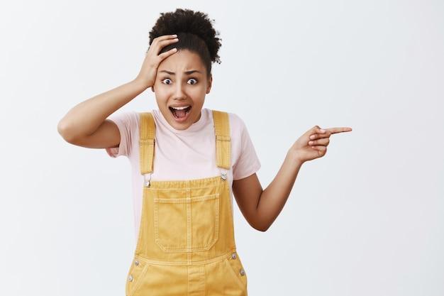 Vrouw wordt verbluft door belachelijke prijzen voor eten in café. geschokt en ontevreden vrouwelijke student met een donkere huid in trendy gele tuinbroek, handpalm op het hoofd, geschokt pratend en naar rechts wijzend
