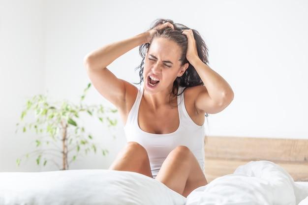 Vrouw wordt wakker met enorme hoofdpijn terwijl ze haar hoofd vasthoudt terwijl ze nog op het bed zit.