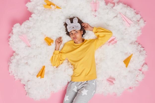 Vrouw wordt wakker na het zien van een onaangename droom kan niet in slaap vallen heeft luie ochtend draagt comfortabele nachtkleding slaapmasker ligt op witte wolk. schot op het hoofd