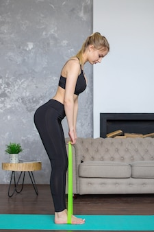 Vrouw workouts thuis met fitness tandvlees, training thuis