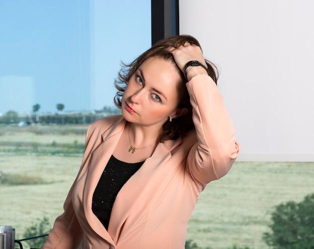 Vrouw zakenvrouw in roze pak speelt met haar bruine haar, past kapsel aan