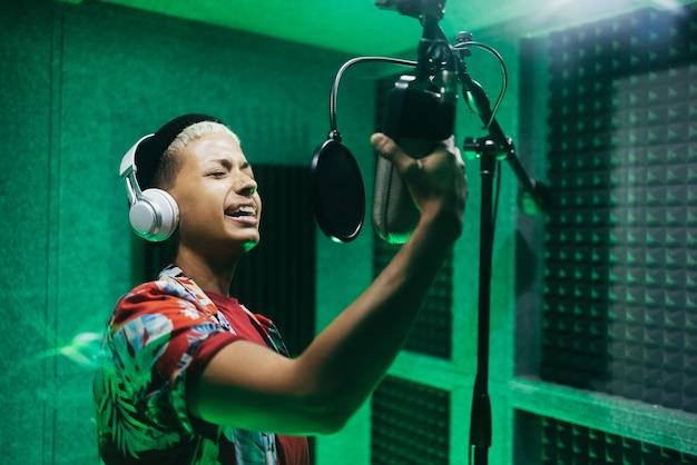 Vrouw zangeres nieuwe muziekalbum opnemen in boetiekstudio - focus op gezicht
