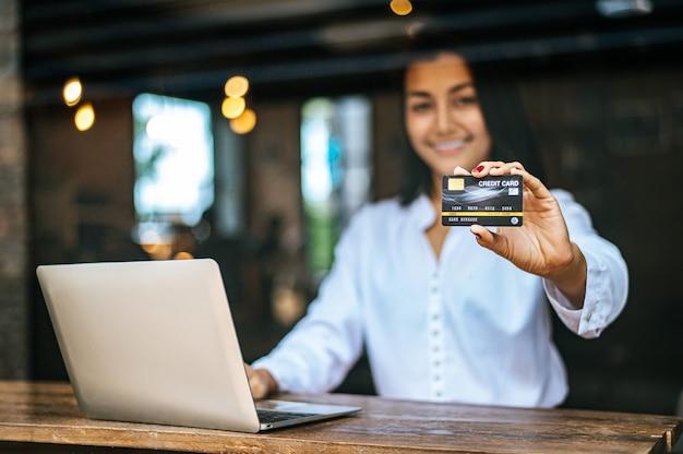 Vrouw zat met een laptop en betaalde met een creditcard in een café